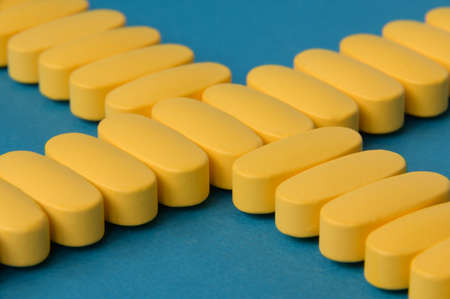healthcare medicine concept of yellow drugs medication pills tablets on blue surface