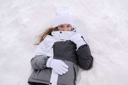 beautiful small girl in warm clothing lean on white snow during winter vacation on ski resort with copy space Foto de archivo