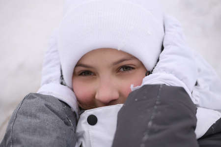 little caucasian girl with frozen ears in warm hat and gloves and jacket during winter travel holiday leisure