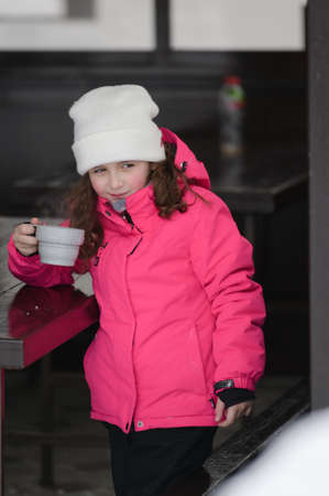 cute little girl in ski suit drinking hot tea from cup during cold winter outdoor leisure activity on mountain resort