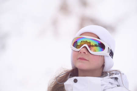 beautiful little girl in ski goggles and wool hat on white snow background in mountains with copy space