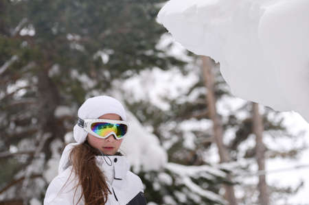 winter lifestyle of little girl in ski suit and goggles on snow trees in forest background with copy space