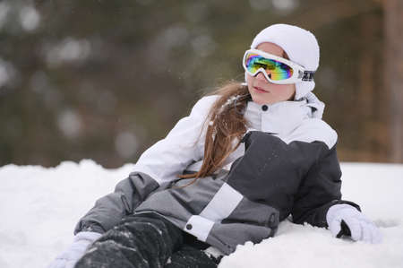 beautiful little girl in ski goggles and suit jacket with gloves lying on white snow in winter park resort