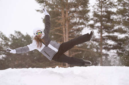 happy active little girl in ski suit jumping on white winter snow during nature outdoor leisure games activity with copy space