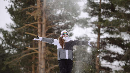 active healthy small kid girl in ski jacket and goggles throwing snow during winter leisure vacation holiday with copy space Foto de archivo