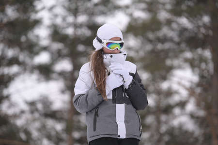 frozen little girl in ski suit jacket and wool cap with warm gloves in winter cold park during christmas vacation Foto de archivo
