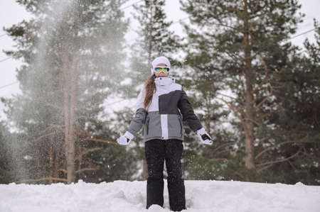 christmas leisure vacation in mountains of little girl in winter warm clothes in snow with fir spruce trees