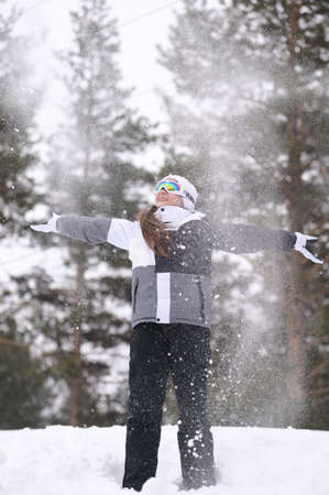 happy smiling little girl wearing ski suit with goggles with falling white snow around in winter park forest during recreation leisure activity