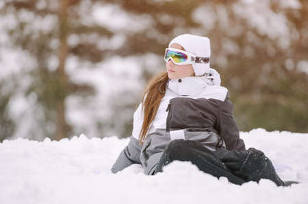 active little healthy sport kid girl in ski suit and goggles sitting in snow at mountain winter resort with copy space during vacation holiday