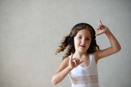 beautiful little girl in headphone listen online music at home dancing with copy space on wall