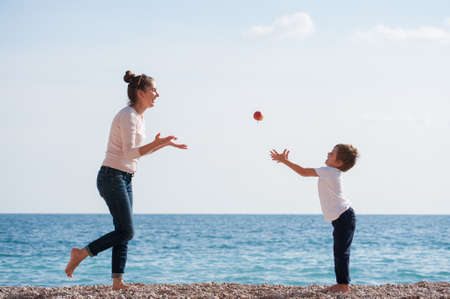 happy active young family of mother woman and offspring child playing with flying apple on sea beach in spring time during leisure agility training