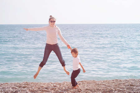 young active family of mother and child jumping on sea spring beach during outdoor leisure activity