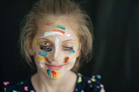 beautiful little caucasian girl with face painted with colorful paint smiling happy