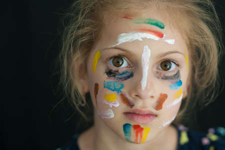 beautiful little caucasian girl with face painted with colorful paint