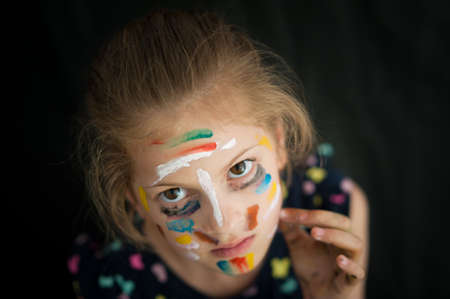 state of mind concept of beautiful little caucasian girl with face painted with colorful paint