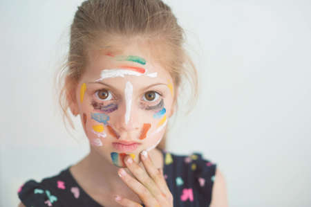 beautiful little serious caucasian girl with face painted with colorful paint with copy space Foto de archivo