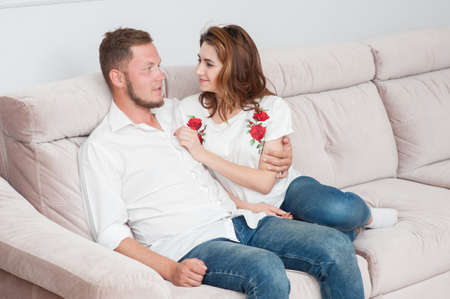 happy beautiful couple young male and female sitting on sofa at home hugging Foto de archivo