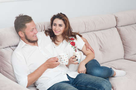 happy young couple caucasian man and woman sitting at sofa with cup of tea at home