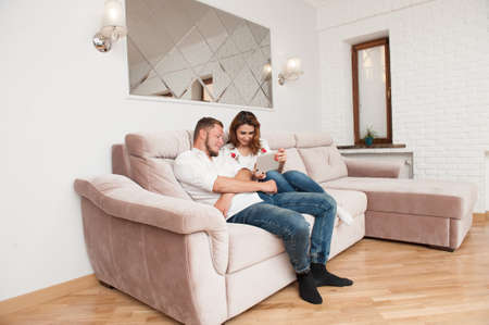 young couple bearded man and woman with mobile gadget sitting on sofa at comfort home online Foto de archivo