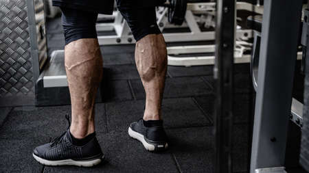 strong calves of young active athlete male in sneakers standing in sport fitness gym near exercise equipment