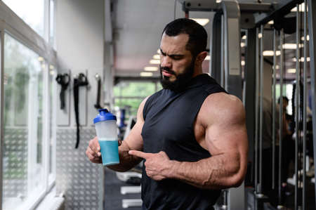 handsome strong young athlete male with beard holding bottle shaker with blue energy drink with copy space in sport gym