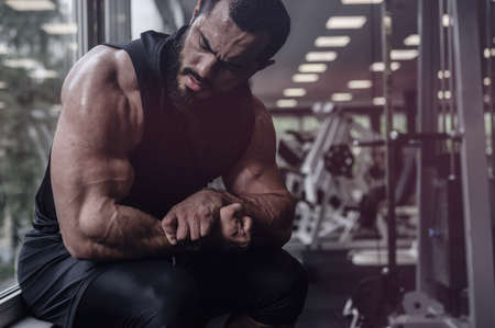 strong young bearded man in black clothes showing muscles biceps sitting near window in sport gym with exercise equipment and copy space Foto de archivo