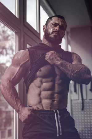 strong young caucasian man athlete with beard showing his perfect physique abdominal muscle near window in sport gym Foto de archivo