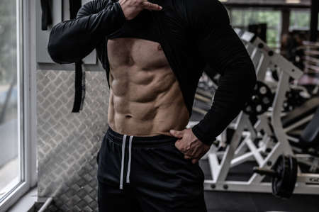 perfect body with abdominal muscles shown by young strong athlete man near window in sport gym with exercise equipment