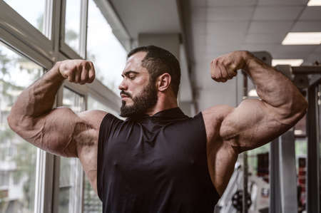 strong young athlete man with beard wearing black tank top showing big double biceps muscle in sport gym with window Foto de archivo