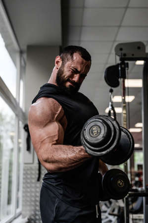heavy bodybuilding workout motivation of strong young bearded man pumping iron lifting heavy weight dumbbells during biceps muscle training in sport gym