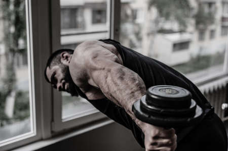 strong young athlete bodybuilder training triceps muscle using iron dumbbell during heavy workout in gym with window Foto de archivo