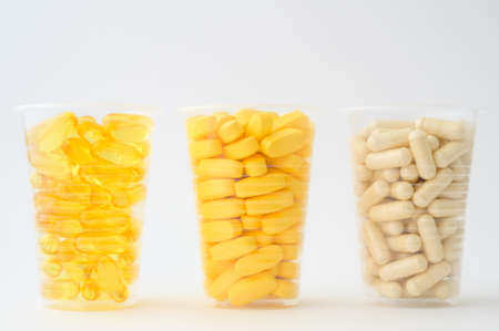 healthy diet nutrition concept of three plastic cups with pills softgels omega3 capsule vitamins tablets on white background with copy space
