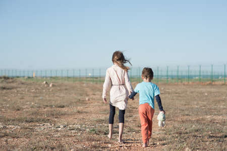 two poor children family brother with toy and thin sister refugee illegal immigrant walking barefooted through hot desert towards state border with barbed fence wire