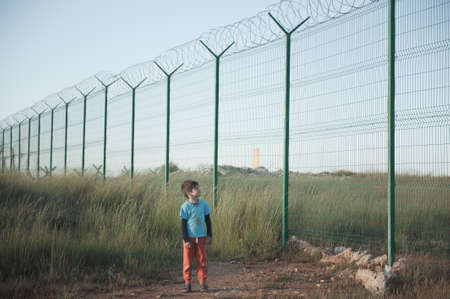 one poor little refugee orphan kid in dirty clothes standing near state border with high fence with razor barbed wire looking on it with hope