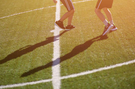 legs in sneakers of two kids on football green field during leisure outdoor activity Foto de archivo