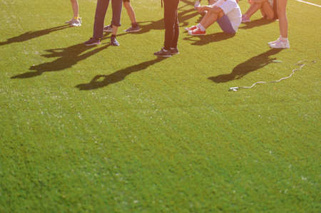 group of children sitting and standing on green soccer football field during pause in sport outdoor leisure training activity in school with copy space