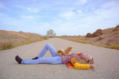 lifestyle concept of young pretty woman in yellow jacket and blue jeans lying on asphalt empty road with little dog on her with sky and copy space during leisure relaxation activity