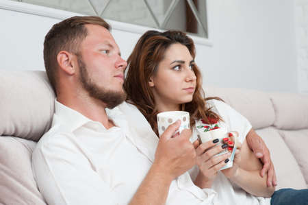 happy young family man and woman with cup of tea watch tv indoors sitting on sofa hugging
