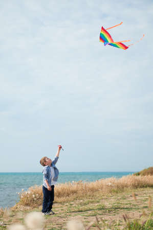 one active healthy small kid holding flying in air colorful kite standing on sea shore with blue sky on sunny summer holiday 版權商用圖片