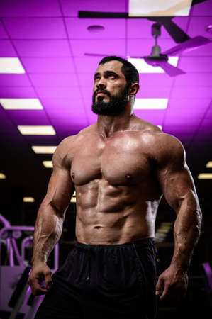 bodybuilding motivation of strong young bearded male in sport gym lit with purple light