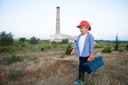 child labor concept of small kid in orange helmet with toolbox going along heavy industry plant factory with high pipe with copy space Stock Photo