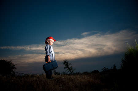 night shift of little boy in red helmet with tool box standing in dusk field with clouds lit with light of factory