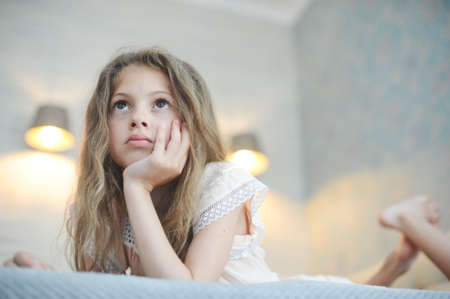 pretty lazy idle little girl with long hair watching TV lying in bedroom