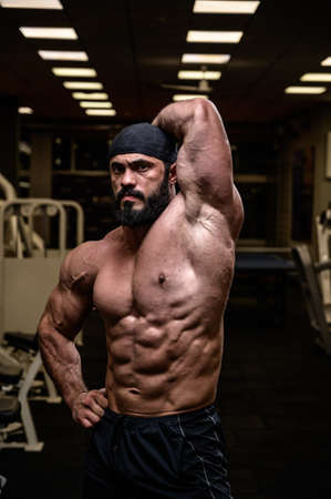 strong bearded male in bandana showing perfect sport physique with abdominal oblique muscle in dark fitness gym