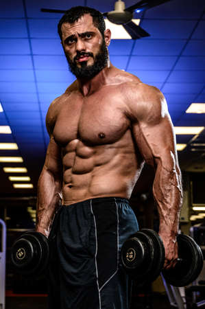 handsome young bearded man with dumbbells in blue lit sport gym during heavy workout training