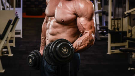 strong physique body of muscle male training pumping biceps with iron heavy dumbbells