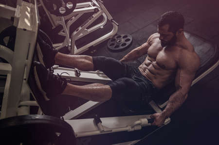 strong young caucasian bearded athlete male leg training in machine for exercise in night gym