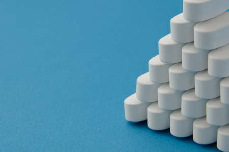 many pharmacological white tablets pills on blue background with copy space Stock Photo