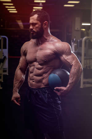 strong young bearded caucasian male with heavy training ball in dark gym Stock Photo