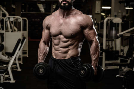 strong athlete bearded man with perfect body muscle with iron dumbbells in fitness sport night gym